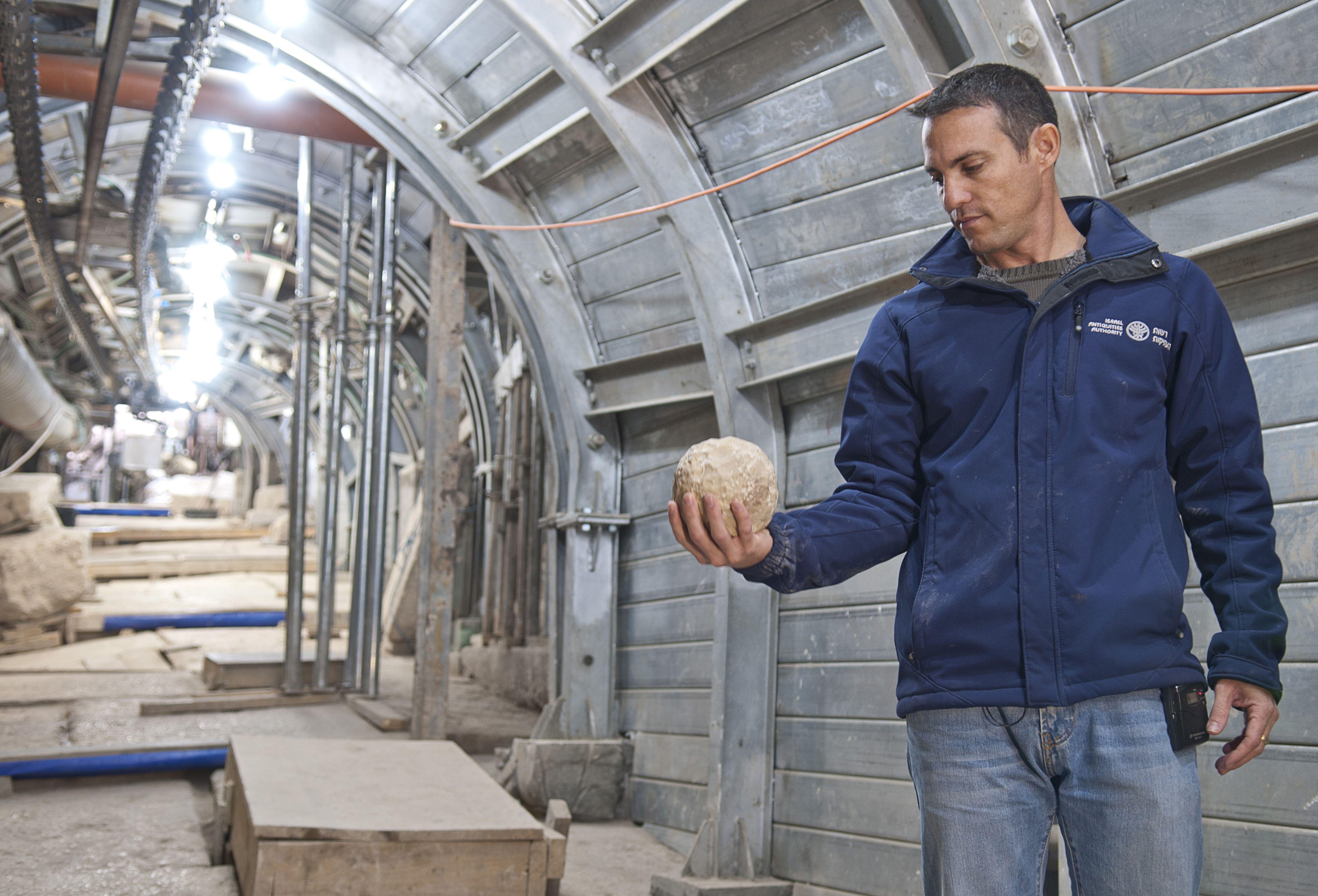 9.נחשון זנטון, ממנהלי חפירת הרחוב, מחזיק כדור בליסטרה שככל הנראה שמש בקרב במהלך המרד הגדול. צילום שי הלוי, רשות העתיקות
