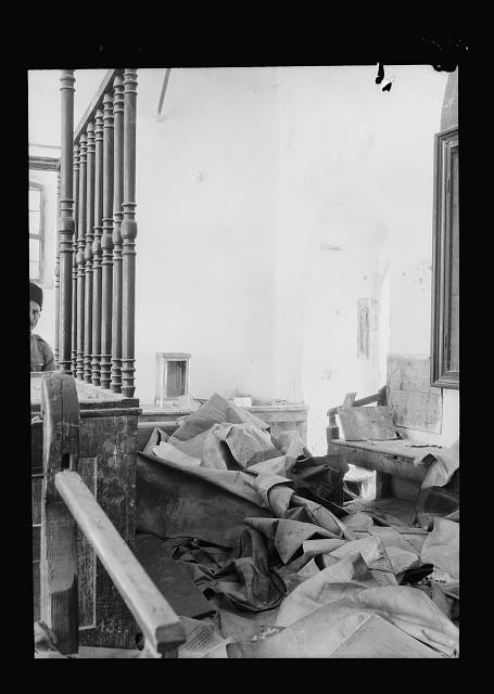 A destroyed synagogue. Torah scrolls strewn on the ground
