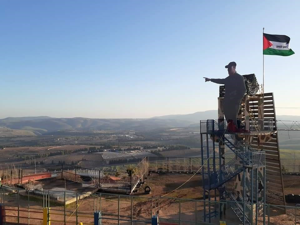 Hizbullah outpost in Southern Lebanon flying the Palestinian flag, showing sculpture of Qasem Soleimani pointing toward the Galilee across the Israeli border.